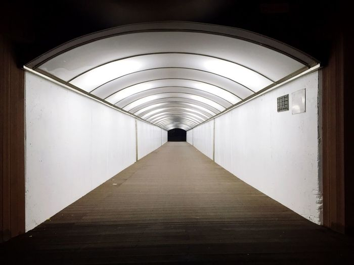 Empty corridor of illuminated building