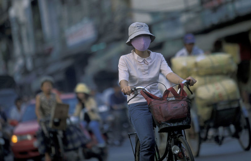 Woman wearing facial mask while riding bicycle on street