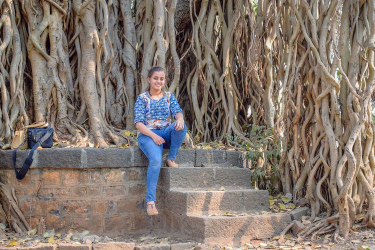 Full length portrait of smiling woman sitting against tree