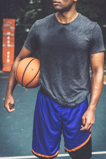 Midsection of man holding basketball ball on court