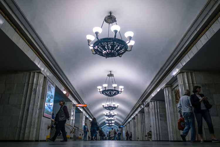 People walking on illuminated ceiling