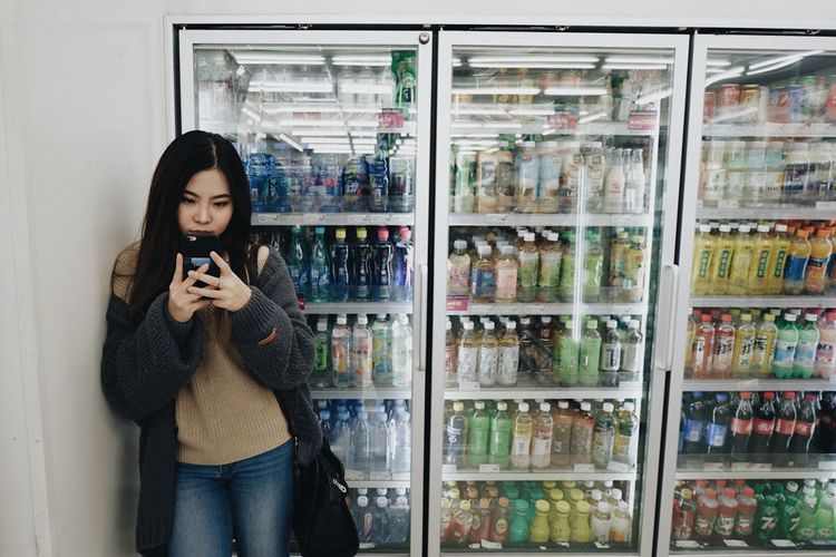 Young woman using phone by refrigerator at market