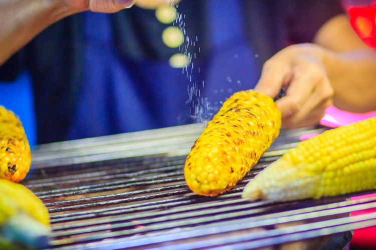 Close up hand of street food vendor while grilling for mixed sweet corn butter. Cook is grilling and sprinkling salt, sugar and butter to the grilled sweet corn on the electric stove. Grilled Corn Grilling Khao San Rd Khao San Road KhaoSan Khaosan Rd. Khaosandroad Close-up Corn Finger Food Food And Drink Freshness Grilled Cornes Hand Holding Human Body Part Human Hand Khao San Khao San Knok Wua Khao San Rd. Khaosan Road Khaosanroad Midsection Night Market Night Market In Thailand One Person Outdoors Preparation  Preparing Food Real People Selective Focus Sprinkling Salt Sweet Corn Butter Sweetcorn Unrecognizable Person Vegetable Yellow