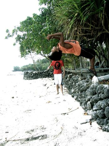 Back Flip Beach Fun Casual Clothing Che Guevara Day Enjoyment Footpath Fresh On Eyeem  Full Length Green Color Leisure Activity Lifestyles Outdoors Palm Trees Person Playful Red Shirt Sand Stone Wall Timing Tree Vacations Weekend Activities Young Adult Young Women