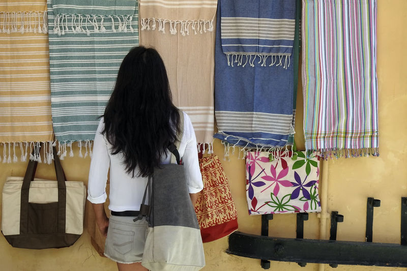 Rear view of woman standing by colorful towels