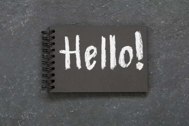 High angle view of hello text on spiral notebook over gray background