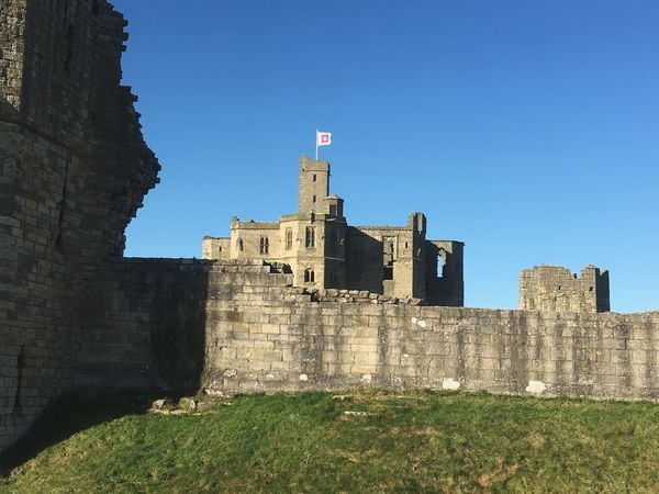 History Architecture Castle Built Structure Building Exterior Fort Day The Past Flag Ancient Outdoors Clear Sky Old Ruin No People Travel Destinations Grass