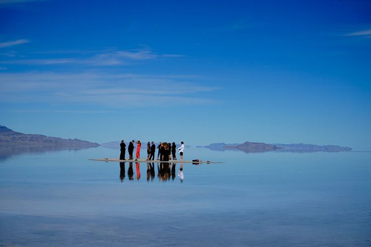 People standing amidst calm lake at bonneville salt flats against sky