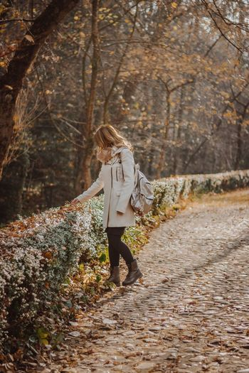 Woman Touching Plant While Walking On Pathway At Park