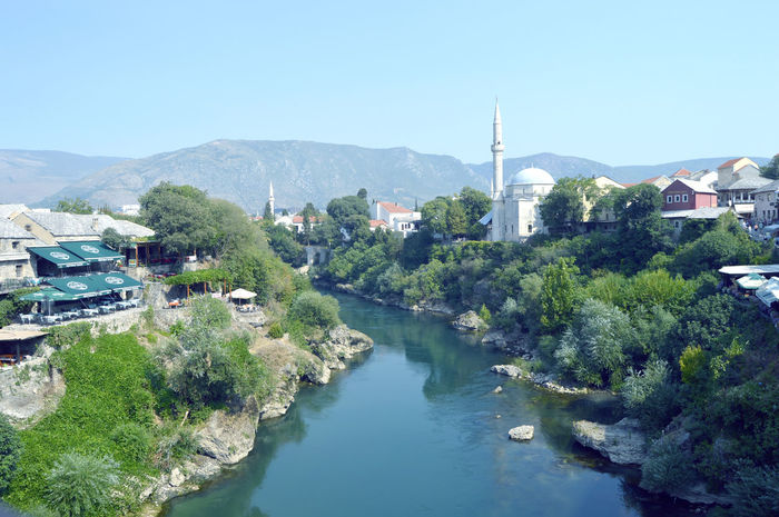Panoramic view from old bridge over Mostar in the Bosnia and Herzegovina Architecture Balkan Bosnia And Herzegovina Green Holiday Mostar Summertime Tourist Travelling Tree View Architecture Beauty In Nature Building Building Exterior Built Structure Clear Sky Day Destination Europe House Mountain Mountain Range Nature Nautical Vessel Neretva No People Outdoors Residential Building River Scenics Season  Sky Summer Tourism Town Tree Urban Water Waterfront