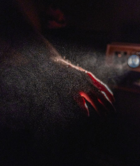 Close-up of hand against red light