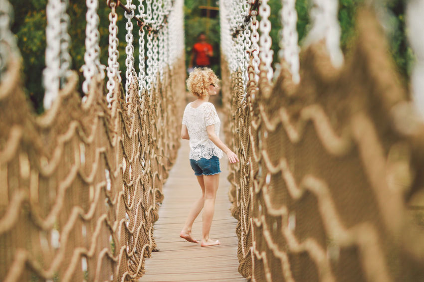 Bare Feet Blonde Blue Jeans Bridge Casual Clothing Curly Hair Day Focus On Foreground Full Length Leisure Activity Lifestyles Nature Outdoors Portrait Rope Selective Focus Sentosa White Shirt Original Experiences Feel The Journey Connected By Travel