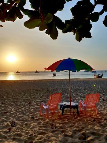Still life of 2 orange chairs and mzlticoloured sunshade on sandy beach during sunset time....