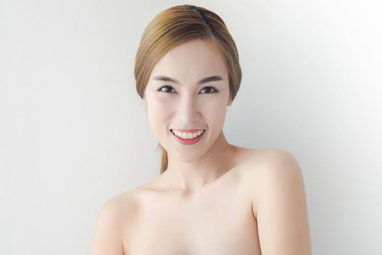 Portrait Of Smiling Topless Young Woman Standing Against Wall