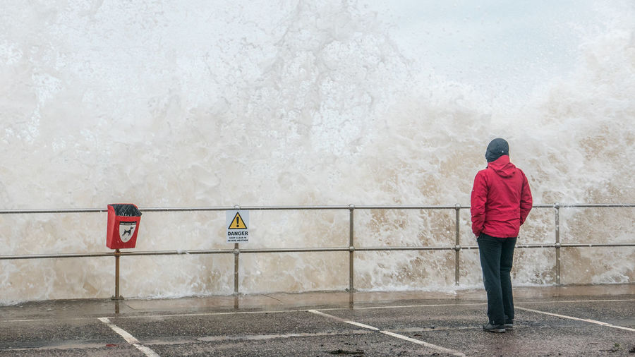 Rear View Of Person Standing On Promenade While Wave Splashing At Sea Shore