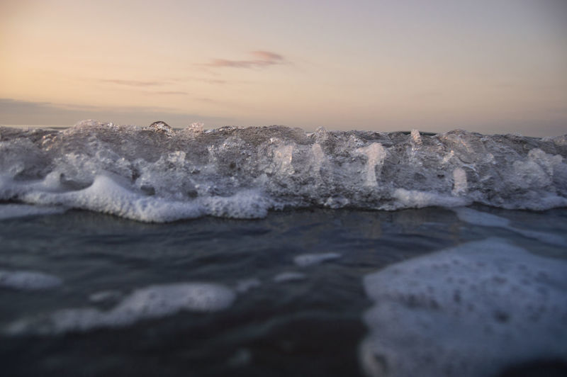 Waves rushing towards shore during sunset