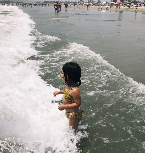 High angle view of boy standing in sea
