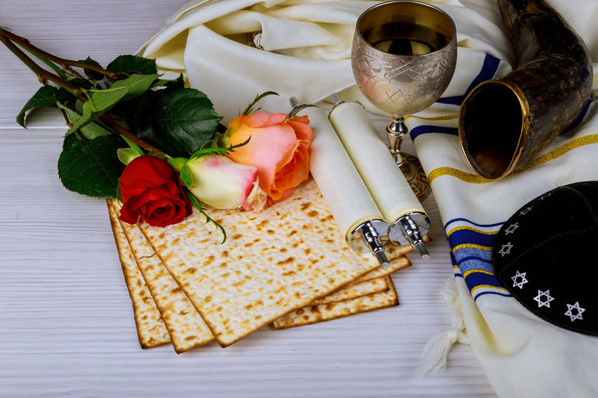 Passover holiday concept with wine and matzoh and spring flowers over background Passover Talith Flower Food And Drink Glasses Kippah Matza Matzah Pessah Prayer Prayer Shawl Religious Celebration Rose - Flower Shofar