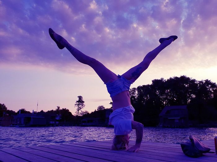 Full Length Of Young Woman Doing Headstand On Pier Over Lake Against Cloudy Sky During Sunset