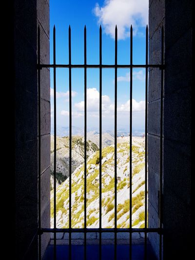 View from Njegos Mausoleum, Lovcen National Park EyeEm Selects Montenegro Lovcen Mausoleum Mountain Mountain Range Blue Sky Security Bar Metal Grate Window History Sky Architecture Window Frame Scenics Mountain Peak Rocky Mountains