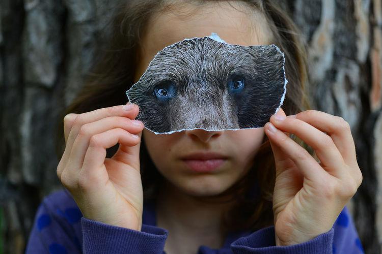 Close-up portrait of girl holding animal eyes sitting outdoors