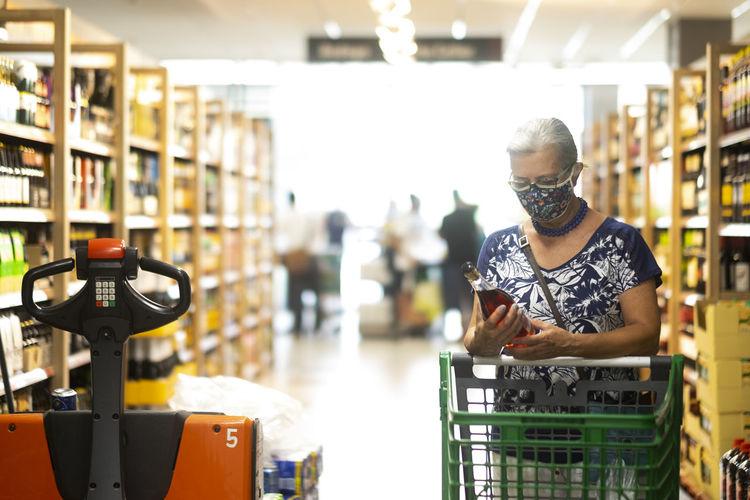 Senior woman wearing flu mask shopping at store