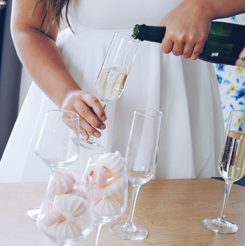 Midsection Of Woman Pouring Champagne In Glasses At Table