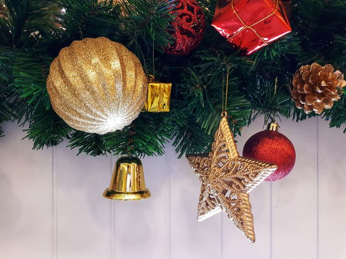Close-up of christmas decorations hanging against white wooden wall