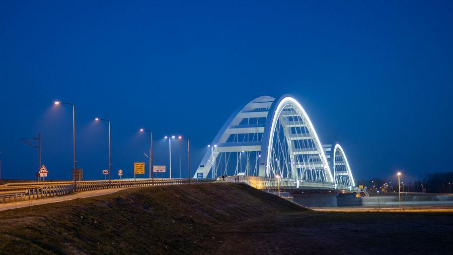 Illuminated bridge against blue sky at night