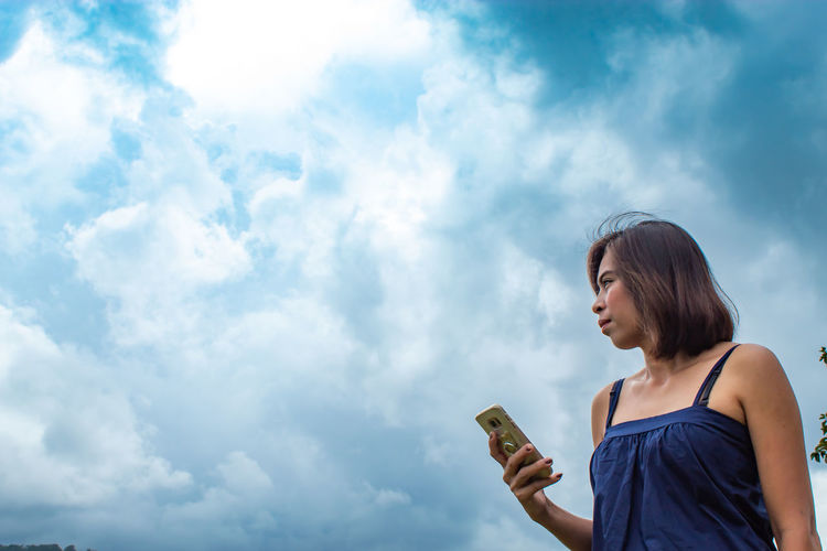 Low angle view of thoughtful woman using phone while standing against cloudy sky