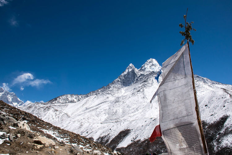 Low Angle View Of Prayer Flag By Snowcapped Mountains Against Sky