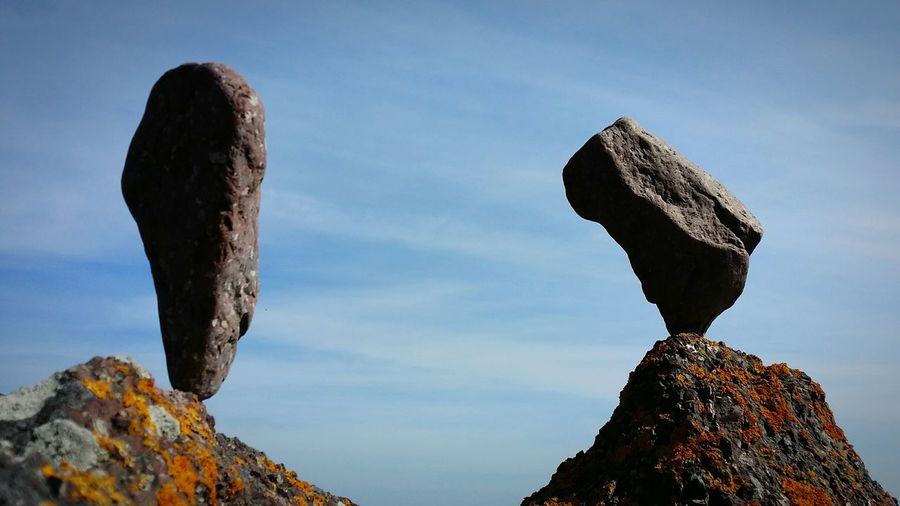 Low angle view of rocks against sky on sunny day