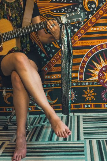 Low section of woman playing guitar
