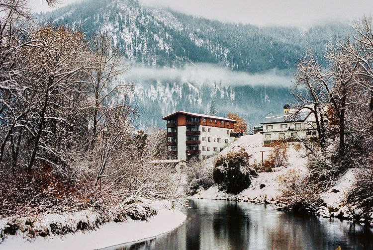 Frozen lake by trees and buildings during winter