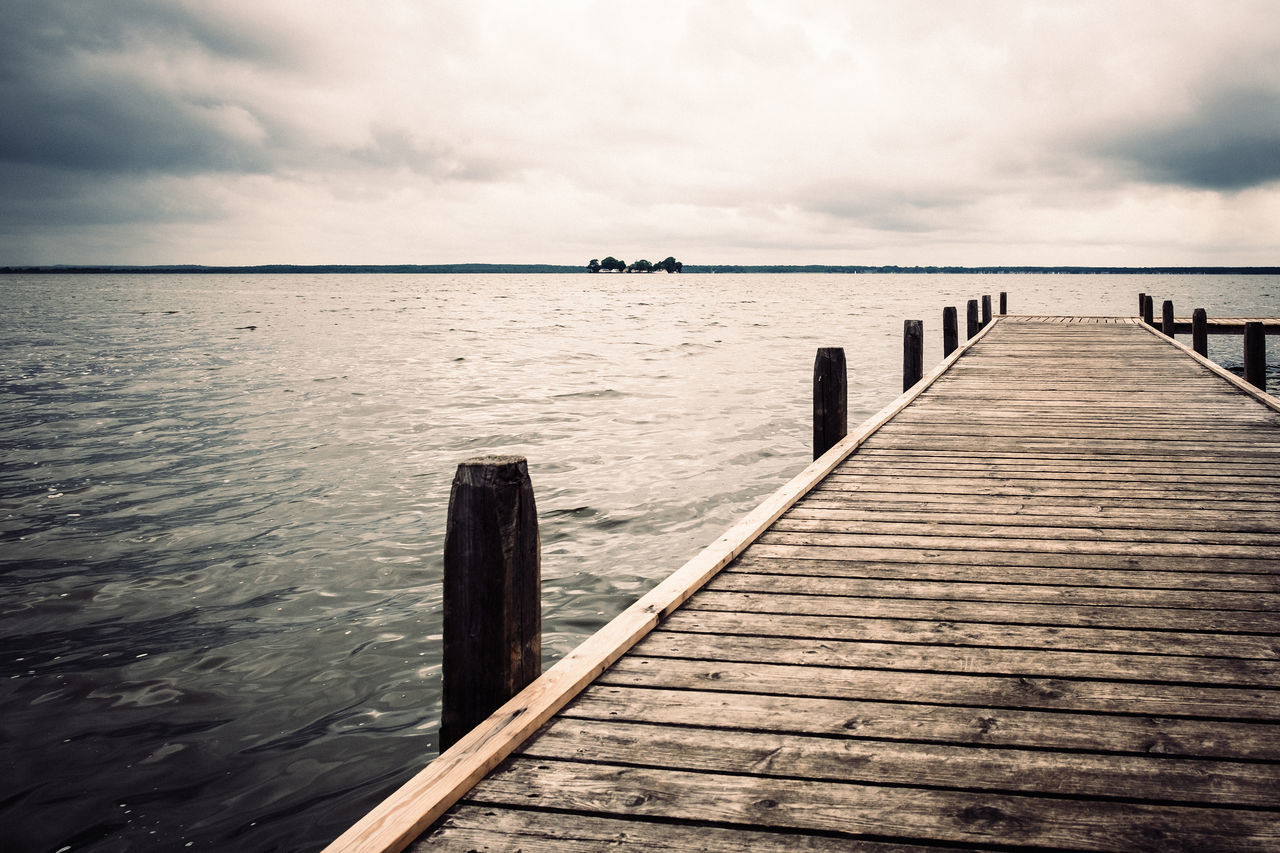 water, pier, sea, tranquil scene, tranquility, wood - material, cloud - sky, sky, jetty, nature, beauty in nature, day, rippled, outdoors, scenics, wood paneling, no people, wooden post, horizon over water, groyne
