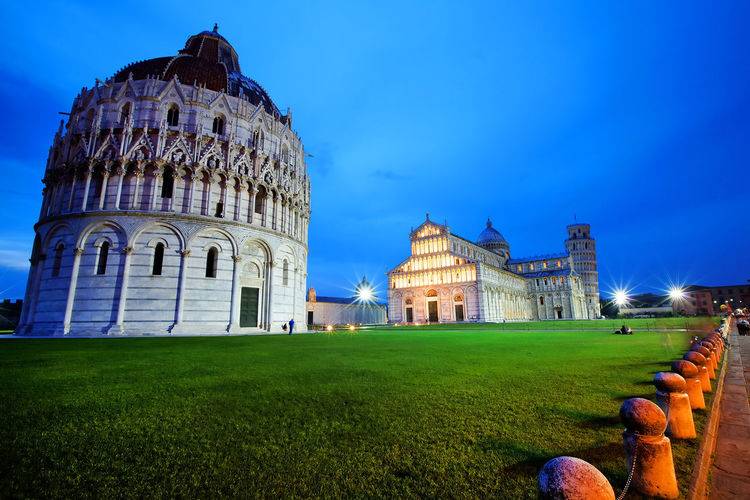 Pisa Cathedral And Leaning Tower Of Pisa With Baptistery Against Blue Sky At Dusk