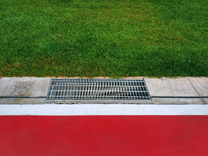 Metal grating by red floor and green grass field