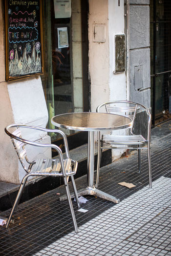 Empty chairs and tables on sidewalk by building