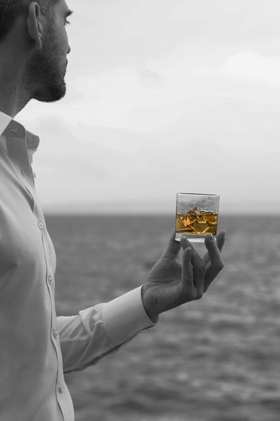 Whiskey in hand by the sea vertical portrait selective color Alcohol Bourbon Clean Cruise Dram Glass Golden Hand Human Element Ice Lifestyle Luxury Portrait Rocks Sailing Scotch Sea Selective Color Shirt Tequila Wealth Whiskey White Yacht