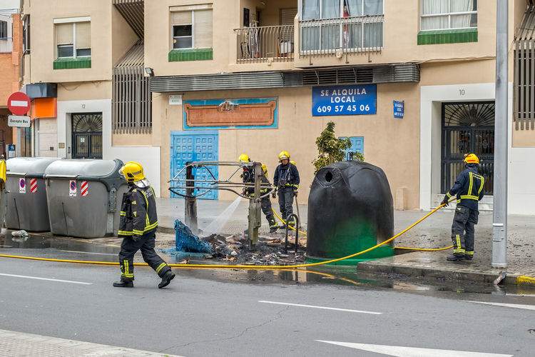 Extinguishing a fire at the garbage can. Malaga, Spain - March 23, 2018. Extinguishing Fires Man Architecture Building Exterior Built Structure City Day Extinguishing Extinguishing Fire Fire Fire Man Garbage Can Men Occupation Outdoors People Real People Reflective Clothing Waste Waste Bin