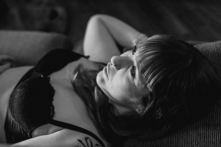 Close-up of sensuous woman relaxing on bed at home