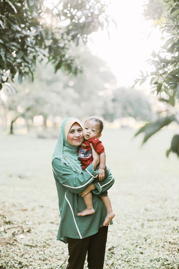 Portrait of smiling mother with son standing at park