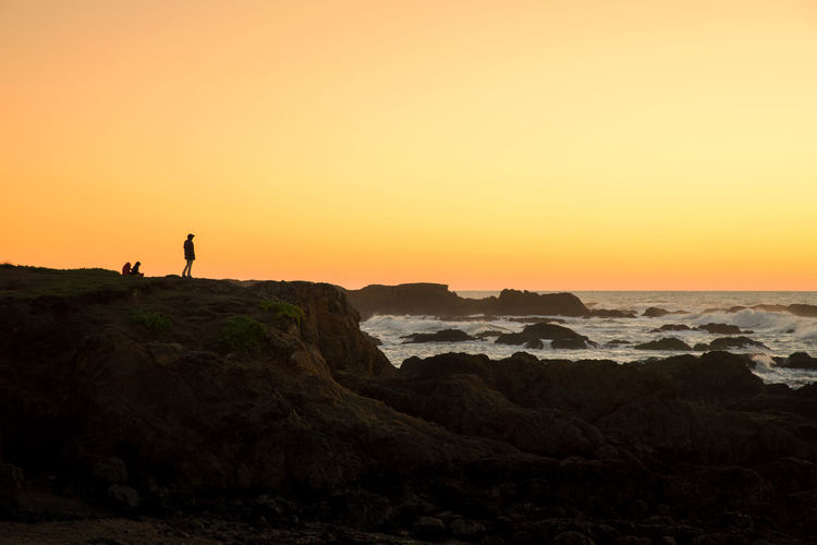 Silhouette people on rocky shore against clear orange sky
