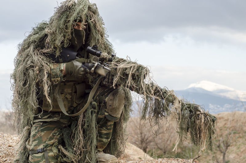 Army man in ghillie suit with rifle on field