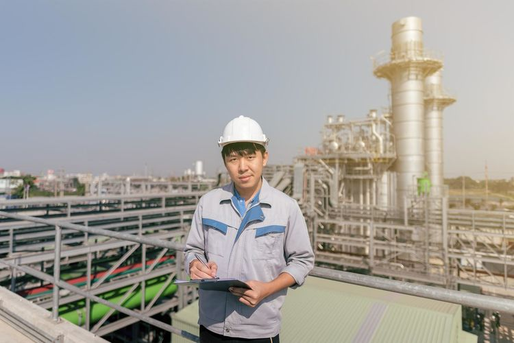 Portrait of worker with checklist standing on roof against sky in factory
