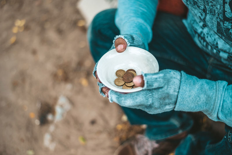 High angle view of beggar with coins in bowl