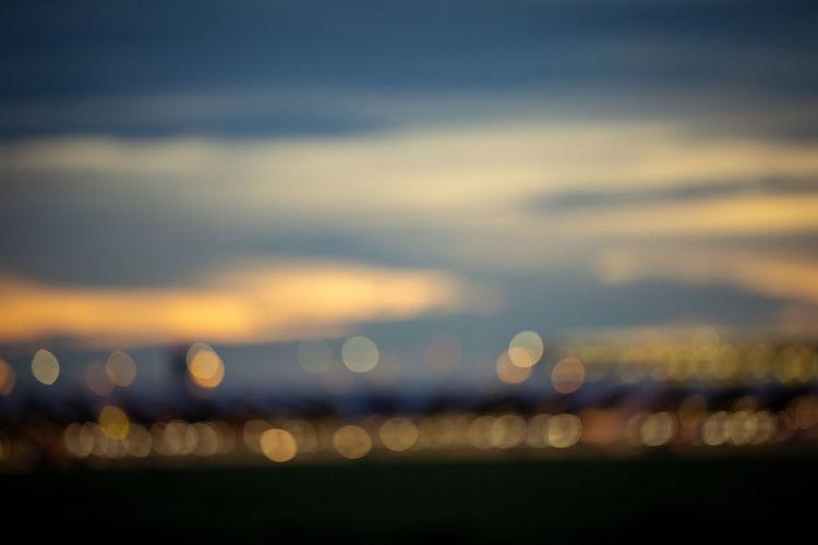 Defocused image of illuminated sea against sky at sunset