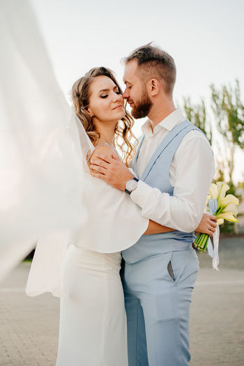 Couple embracing while standing outdoors
