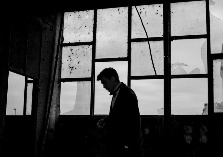 a silhouette of a man Architecture Building Built Structure Contemplation Day Indoors  Leisure Activity Lifestyles Looking Men One Person Real People Side View Silhouette Sky Standing Transparent Waist Up Window