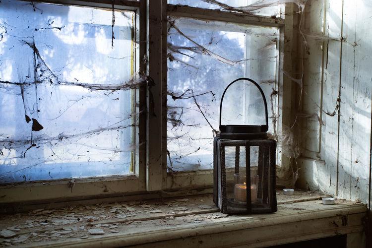 Abandoned building seen through broken glass window